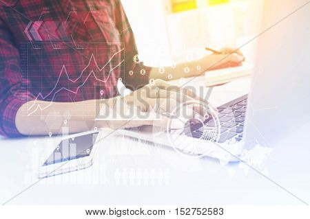 Close up of girl's hands working at laptop and taking notes simultaneously. Graphs and world map on the foreground. Toned image. Double exposure.