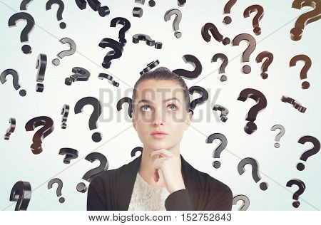 Close up of thoughtful young woman with her hand on the chin standing in room full of floating question marks. Concept of solution finding