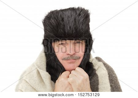 elderly man in fur hat with ear flaps covers his ears from the cold