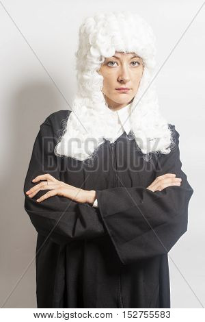 Female judge wearing a wig and Back mantle on white backgriund