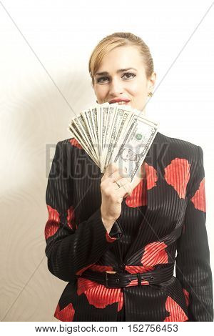 Portrait Smiling businesswoman in suit with dollars in her hand on wallpaper background