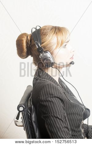 Portrait of happy support phone operator in headset at workplace