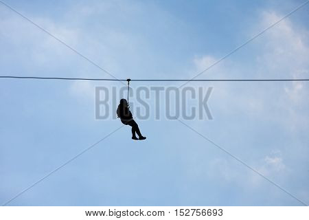Hanging silhouette of a man on a wire (Canopy extreme sport)