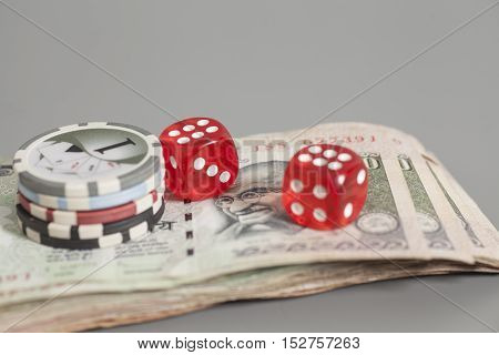 Poker chips and red dice on Indian Currency Rupee bank notes isolated on gray background