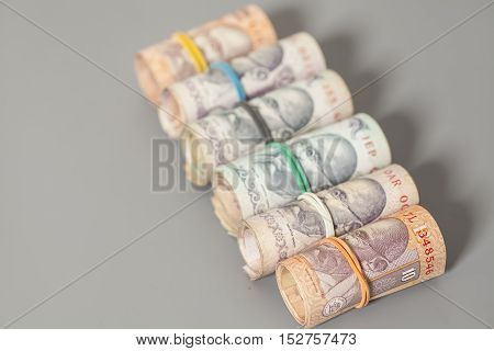 Roll of Indian rupee banknotes isolated on gray