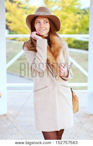 Elegant caucasian redhead woman with freckles and green eyes in fedora hat and beige coat with fur. City street fashion.