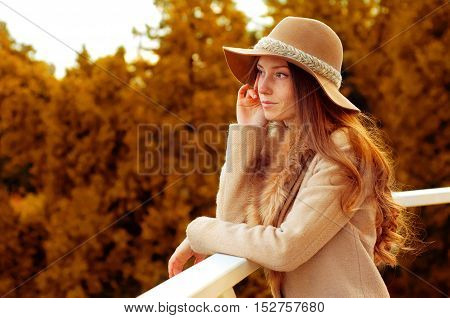 Woman with long red hair fedora hat and fur coat standing on the balcony in the woods in autumn. Melancholic mood.