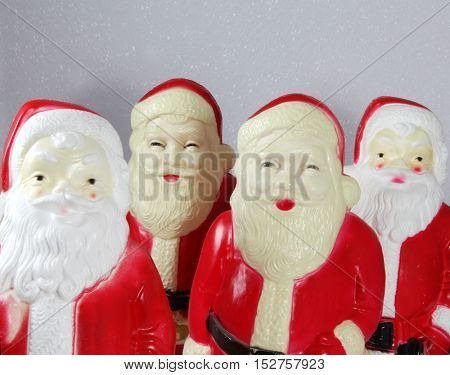 A quartet of vintage creepy plastic Santa Claus decorations for Christmas