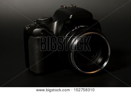 Professional modern DSLR camera with aperture lens isolated on black