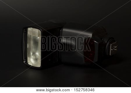 Camera flash speedlight on a black background