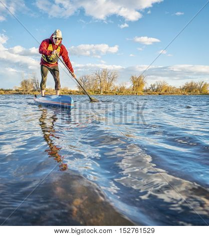 paddling stand up paddleboard on lake in Colorado, fall scenery with wind