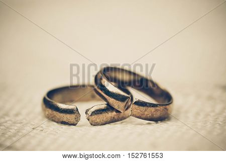 Two broken golden wedding rings / Divorce concept