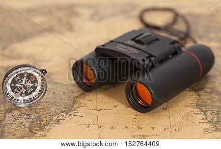 Binocular optics and compass on map. travel strategy.