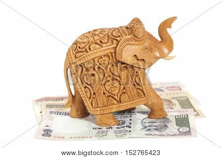 Wooden elephant sculpture on Indian Rupee banknotes isolated on white