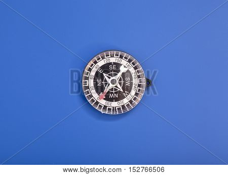 Compass isolated on a blue background .