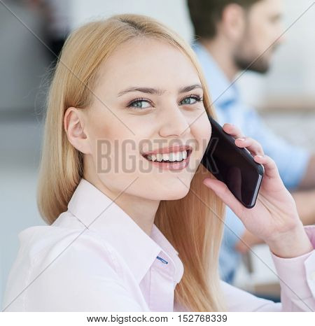 Attractive young businesswoman is communicating on mobile phone. She is looking at camera and smiling. Her male colleague is sitting on background