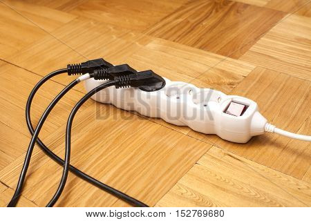 Many plugs plugged into electric power bar on floor