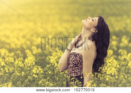 Beautiful woman in meadow of yellow flowers with face up. Attractive genuine young girl enjoying the warm summer sun in a wide green and yellow meadow. Part of series.