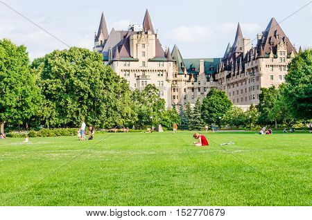 Ottawa, Canada - July 24, 2014: People in Majors Hill Park by Fairmont Château Laurier hotel