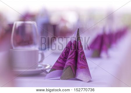 Beautiful purple napkins in row on a table from catering. High class arrangement for e.g. a wedding birthday or business meeting.