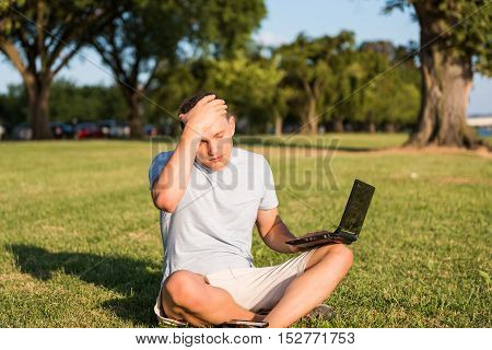 Sad young man with laptop and smartphone, sitting outside in green grass in park placing hand on head due to stress headache and eyes closed looking down
