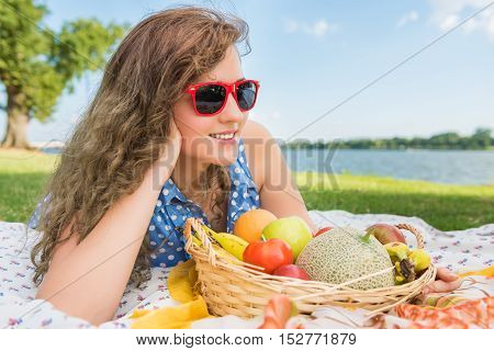 Young woman in red sunglasses lying down and smiling on picnic blanket with fruit basket near Potomac River in Washington, DC