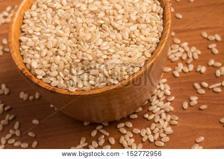 Wholegrains Cateto Rice. Integral over a wooden table