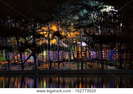 Amazing dark night park view with small houses ladders roads and steps. Colorful lights are reflected in water.