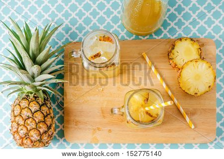Pineapple Slices And Juice In Glassware On Wooden Table