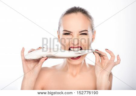 Passionate young woman is biting fish with wildness. She is standing and looking at camera with greed. Isolated