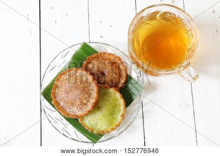 Kuih pinjaram and tea on white wooden palette
