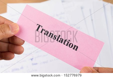 hand holding translation pink card over blur document