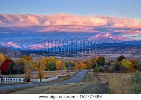 Long's Peak lights up at sunrise as a rural country road leads into the fall trees