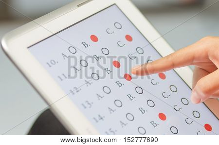 student testing in exercise exams answer on a tablet with multiple-choice questions of e-learning by finger clicking : education concept