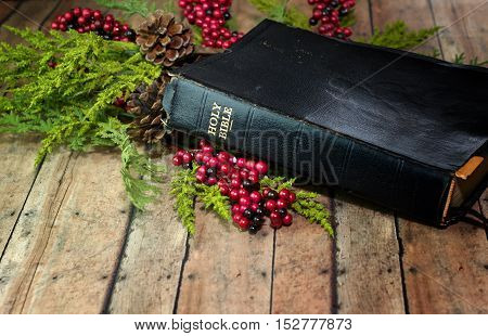 An Old Rustic Bible with Christmas Garland berries and pine cones on a wood plank board