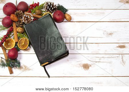An Old Rustic Bible with Christmas Garland Potpourri consisting of dried fruit oranges pomegranate nuts and pine cones on a wood plank board with room for copy space