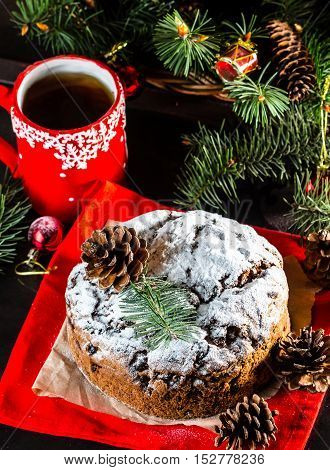 Christmas composition. Christmas cake pan de pasqua, red mug of tea and Christmas New Year decoration - fir brunches, fir and pine cones, New Year balls, red napkin on black background
