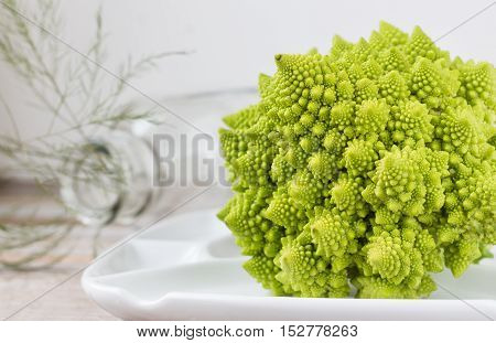 horizontal close up image of a romanesco cauliflower in a white plate on one side of image with room for text on the other side.