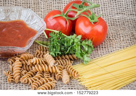 horizontal image of raw spaghetti and whole wheat pasta with tomato on the vine and a dish of salsa on burlap background.