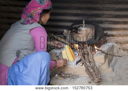 Himachali woman cooking food on wood fire stove(chulha) in her kitchen, Shimla, Himachal Pradesh, India.