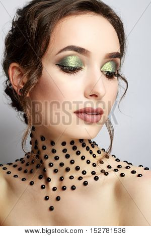 Elegant young lady with evening smart make up and beads on her neck. Make-up of woman eye with khaki eyeshadow. Beauty portrait of a girl model with make-up green eyes. Creative Professional makeup.