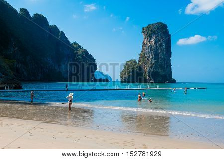 The beach and floating dock with amazing view of huge rock and blue sky on a sunny day