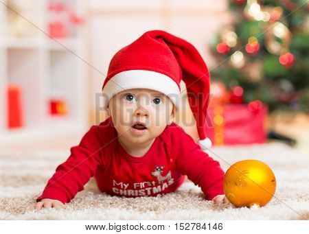Funny baby lying on tummy wearing Santa hat and suit on floor in front of Christmas tree