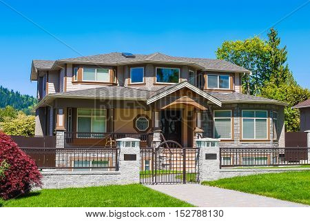 Luxury residential house with iron fence and green lawn in front