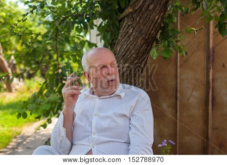 Portrait of Ukrainian elderly peasant sitting under tree shadow and smoking cigarette at summer season