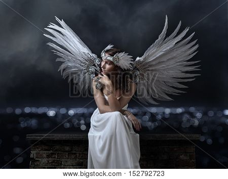 Beautiful Woman In White Dress With Angel Wings On A Background Of Night City