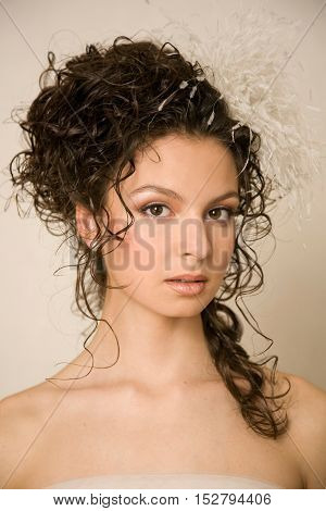 Young stylish smiling bride with feather hairpin in her hair