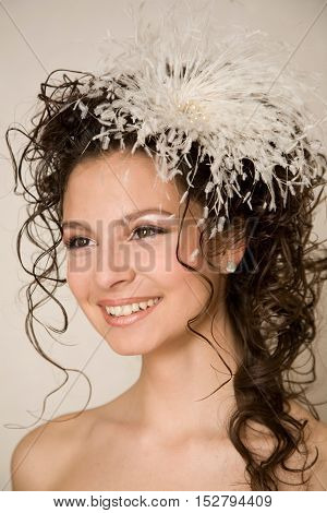 Sweet smiling bride with feather hairpin in her hair