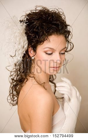 Young beautiful bride with her hands near her chest and feather hairpin in her hair