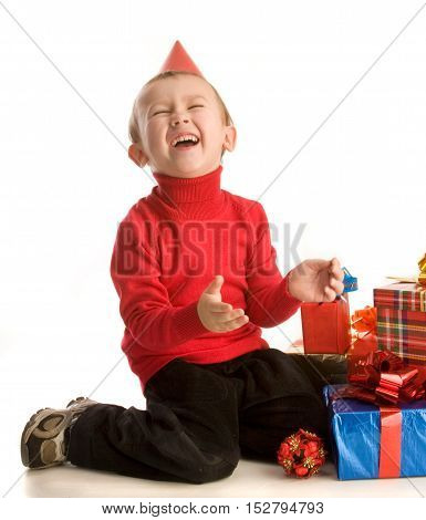 Little boy with presents is sitting and laughing; isolated on white background